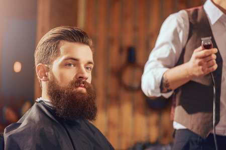 electric razor: Like the result. Bearded handsome man sitting in the barbershop while barber standing with electric razor nearby