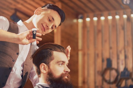 skillful: Like what you do. Positive delighted skillful barber holding hair brush and expressing gladness while styling hair of his client Stock Photo