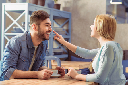 some: Have some fun. Positive jubilant romantic couple sitting in the cafe at the table and drinking coffee while expressing joy Stock Photo
