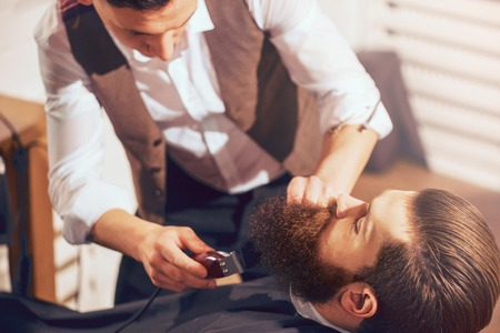 pleasant: Creative process. Pleasant professional barber holding electric razor and cutting beard of his handsome client Stock Photo