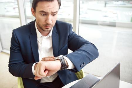 Het is te laat . Knappe verraste mens zit aan de tafel en kijkt op zijn horloge terwijl het uitdrukken wonder
