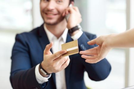 Bezahle es ab. Close up der Kreditkarte in der Hand eines Geschäfts es der Kellnerin und reden über Handy zu geben
