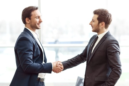 gladness: Nice to meet you. Pleasant handsome businessmen smiling and shaking hands while expressing gladness