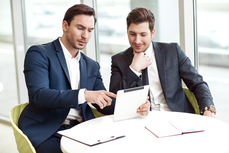 Have a look. Pleasant handsome business partners sitting at the table and looking at the screen of the tablet Stock Photo