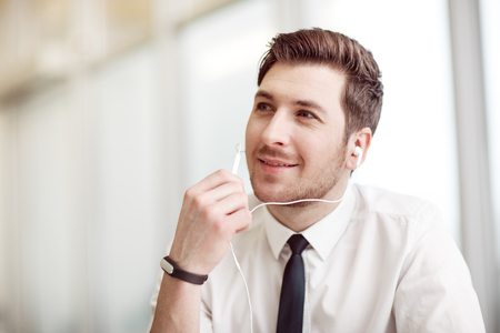 gladness: Feel the rhythm. Pleasant handsome man holding headphones and listening to music while expressing gladness.