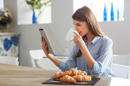 lunch table: Modern way of life. Cheerful attractive woman sitting at the table and using tablet while drinking coffee Stock Photo