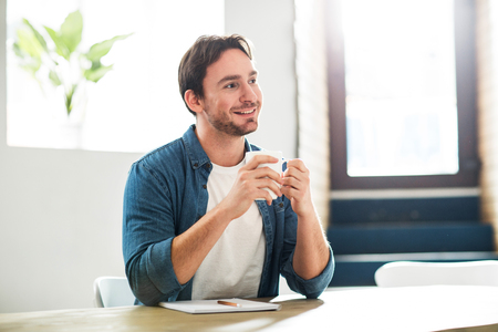 expressing joy: Take your time. Delighted smiling handsome man drinking coffee and sitting at the table while expressing joy