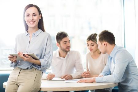 Real workaholic. Mooie aantrekkelijke vrouw leunend op de tafel en de tablet, terwijl haar collega's bespreken project zitten in de achtergrond
