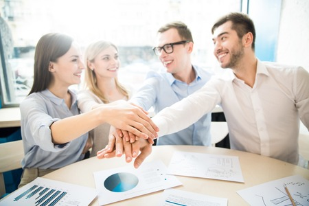 expressing joy: We will achieve success.  Pleasant delighted colleagues sitting at the table and holding their hands together while expressing joy Stock Photo