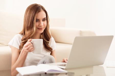calentar. Muchacha hermosa agradable que bebe té y que usa la computadora portátil mientras que se sienta en el piso cerca de la tabla