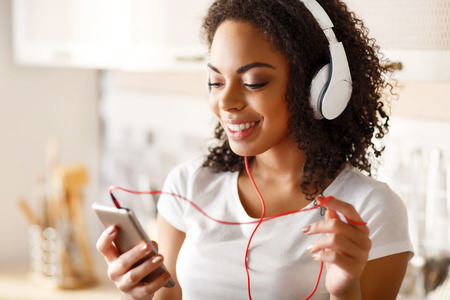 enjoyable: Rise your spirit. Positive smiling enjoyable girl holding cell phone and listening to music while  expressing gladness