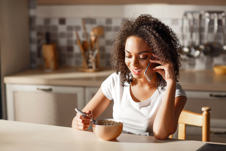 comiendo cereal: Get some energy. Cheerful attractive positive girl sitting at the table and eating cereal while talking on smartphone