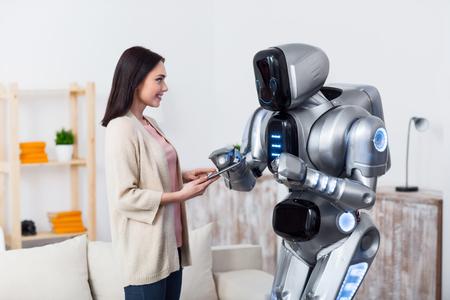 도와주세요. 명랑 긍정적 매력적인 여자 태블릿을 사용하여 로봇에주고있는 동안 미소