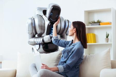 Sólo sonríe. Encantado de chica positiva atractiva sentada en el sofá y tocar robot mientras lo mira