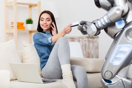 talking robot: Pay it off. Cheerful delighted attractive girl sitting on the couch and talking on smart phone while giving credit card to the robot