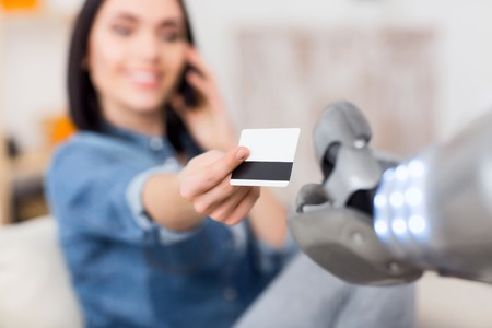 talking robot: Here you are. Selective focus of credit card in hands of pleasant smiling  attractive girl talking on cell phone and holding it while giving to the robot