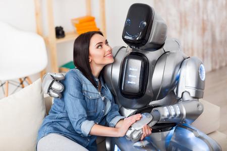 Amigos verdaderos. chica encantados positivo y el robot se sienta en el sofá y que expresa alegría, mientras que la unión entre sí
