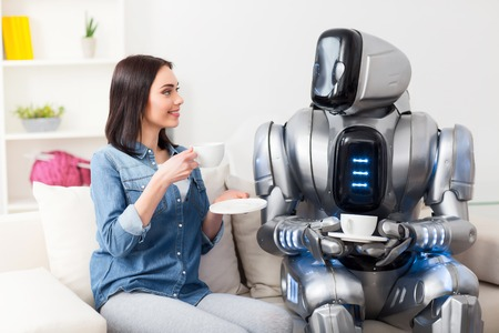 Spend time with pleasure. Cheerful delighted beautiful girl  drinking coffee and resting on the couch with the robot while having a nice discussion  talk