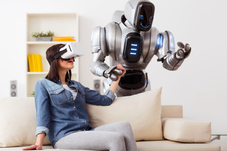 Involved in fun. Cheerful content  smiling girl using virtual reality device and   holding hand of the  robot while sitting on the couch