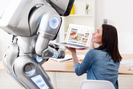 talking robot: Have a look. Pleasant delighted girl sitting at the table and showing  screen of the laptop while talking with  the robot Stock Photo
