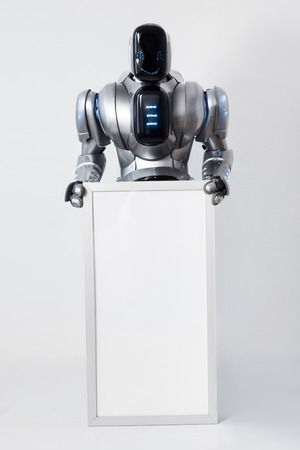 gladness: Overwhelmed with gladness.  Delighted smiling modern robot holding white signboard and smiling while expressing delight Stock Photo