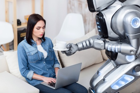 cheerless: Out of temper. Modern big robot giving cup of coffee to a cheerless   attractive girl who is sitting on the couch and using laptop