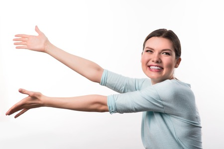 overjoyed: Look here. Positive overjoyed beautiful girl holding her hands up and pointing aside while expressing gladness Stock Photo
