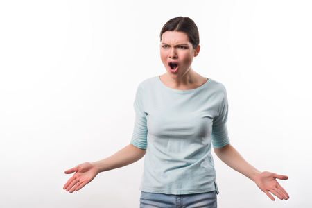 cheerless: Can not keep emotions inside. Cheerless  irritated beautiful girl screaming and  displaying temper while standing isolated on white background