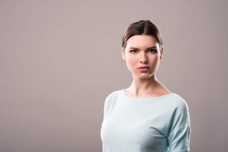Express confidence. Pleasant serious beautiful girl looking at you and feeling assured while standing isolated on grey background Stock Photo