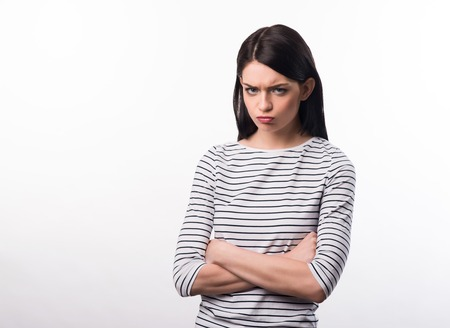 cheerless: Out of temper. Gloomy  cheerless girl folding her hands and expressing dissatisfaction while standing isolated on white background Stock Photo
