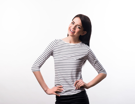 hands on waist: Stay positive. Cheerful beautiful content girl holding her hands on the waist line and smiling while standing isolated on grey background Stock Photo