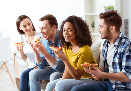 enjoyable: Enjoyable time.  Content positive happy friends sitting on the couch and eating pizza while resting together
