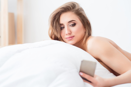 pleasant: In touch with world. Pleasant charming delighted woman lying in bed and holding cellphone while resting Stock Photo