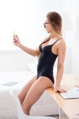 desired: Desired by everyone.  Delighted attractive magnetic woman leaning on the table and using cellphone while seducing you