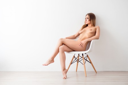 naked youth: Mysterious  glance. Confident attractive slim nude woman sitting in the chair and looking aside while seducing you