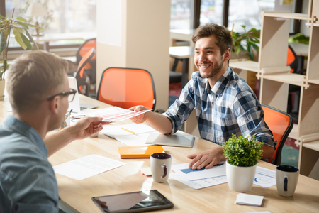 gladness: Here you are. Cheerful handsome smiling pleasant colleagues sitting at the table and giving paper to each other while expressing gladness