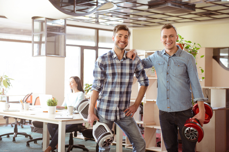 gladness: Time to get rest. Cheerful handsome positive guys expressing gladness and holding mini segways while standing in the office Stock Photo