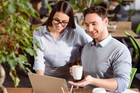 handsom: Help me. Cheerful handsom smiling man drinking coffee and sitting at the table while using laptop with his colleague who is standing nearby