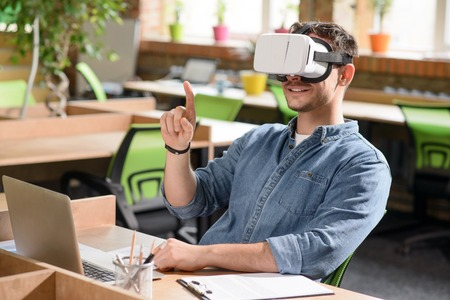 VIRTUAL REALITY: I see new world. Cheerful handsome pleasant  man sitting at the table and expressing positivity while wearing virtual reality device