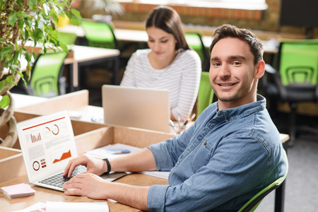 gladness: Best work. Cheerful content smiling man working on the laptop and  expressing gladness while his colleague sitting at the table in the background