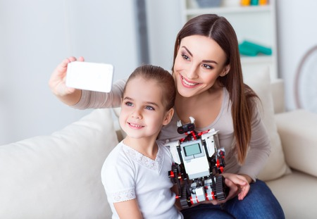 say cheese: Say cheese. Cheerful pleasant mother holding cellphone and making selfies while playing with her daughter Stock Photo