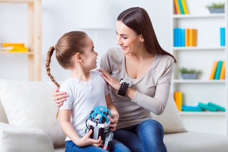 talking robot: Under protection of mother.  Pleasant beautiful woman sitting on the couch with her daughter and talking while playing with robot Stock Photo