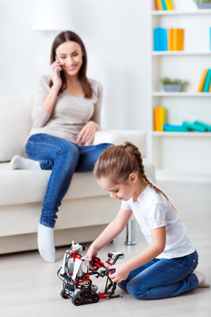 talking robot: Involved in game. Cheerful cute little girl playing on the floor with robot while her mother sitting in the background and talking on cell phone