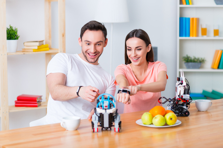 gladness: Remember childhood. Cheerful delighted positive couple sitting at the table  and playing with robot while expressing gladness