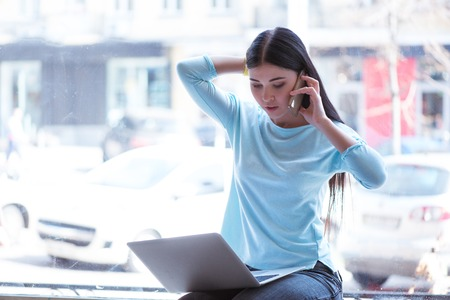 important phone call: Important call. Pleasant beautiful concentrated woman talking on mobile phone and using laptop while sitting on the window sill Stock Photo