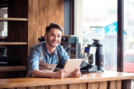 gladness: Ready to work for my guests. Pleasant smiling delighted handsome barista standing at the counter and expressing gladness while using tablet Stock Photo