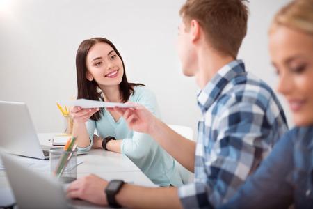 So nett. Junge lächelnde und fröhliche Studenten studieren gemeinsam in der Klasse mit dem Laptop und einander helfen