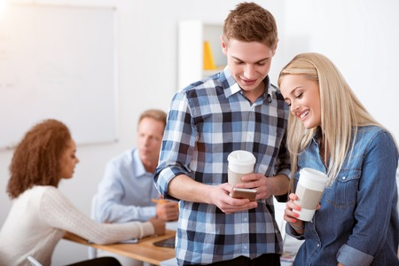 having a break: Coffee break. Smiling pleasant young students drinking coffee and laughing while having a break