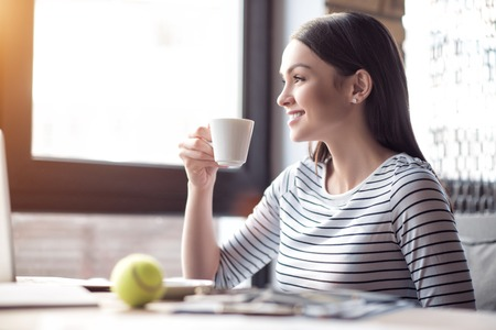 gladness: Open your mind.  Pleasant cheerful smiling beautiful woman sitting at the table and expressing gladness while drinking coffee