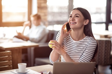 overjoyed: Like communication.  Overjoyed smiling beautiful woman talking on cellphone and expressing gladness while her colleague sitting in the background Stock Photo